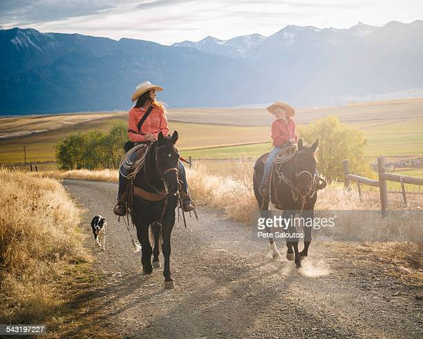 Caucasian mother and son riding horses on ranch