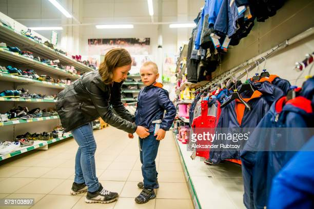 Caucasian mother and son shopping in clothing store
