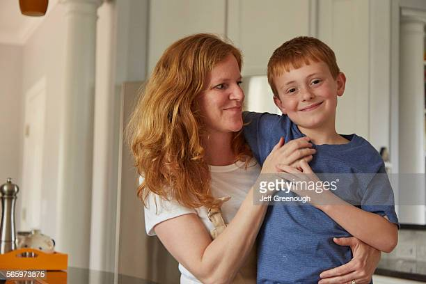 Caucasian mother and son smiling in kitchen