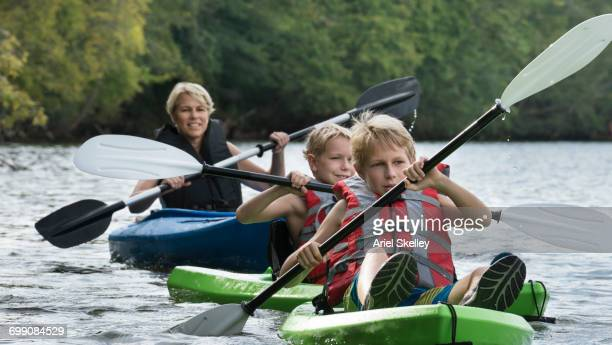 Caucasian mother and sons kayaking in river