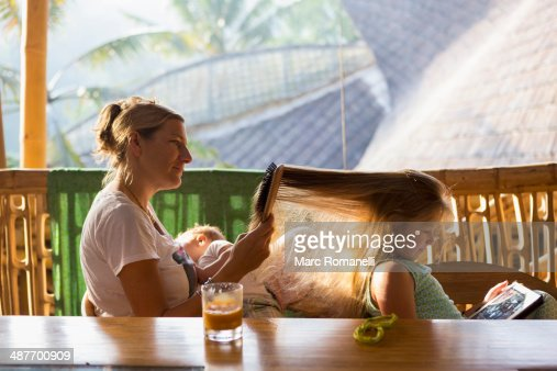 Caucasian mother brushing daughter's hair on patio : Stock Photo