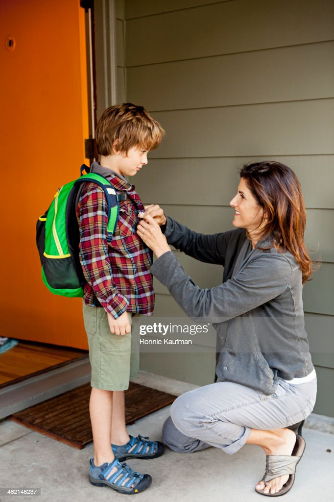Caucasian mother buttoning son's shirt : Stock Photo