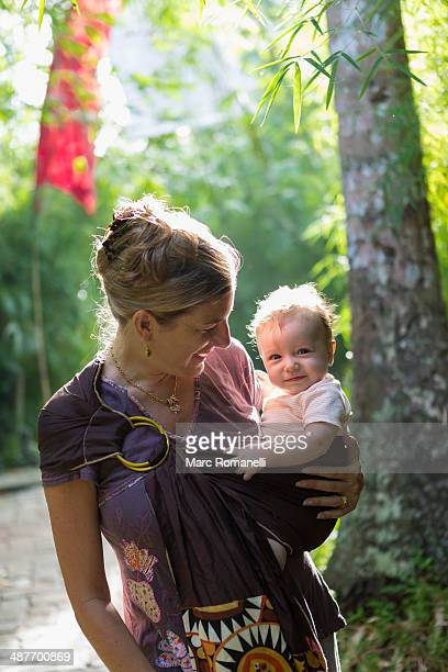 Caucasian mother carrying baby in rainforest