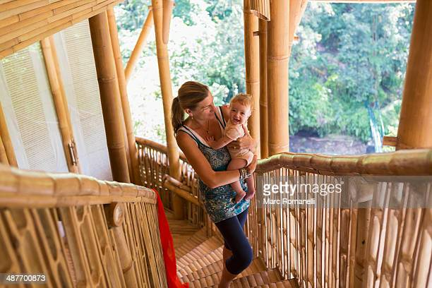 Caucasian mother carrying baby up stairs