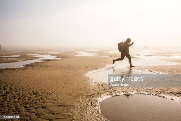 Caucasian mother carrying daughter jumping over puddle at beach
