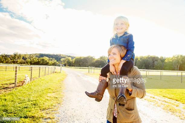 Caucasian mother carrying daughter on shoulders on rural road