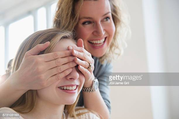 Caucasian mother covering eyes of daughter