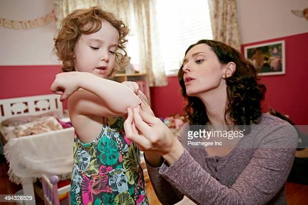 Caucasian mother examining daughter's scrape