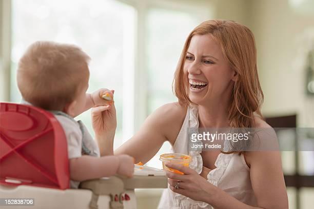 Caucasian mother feeding son