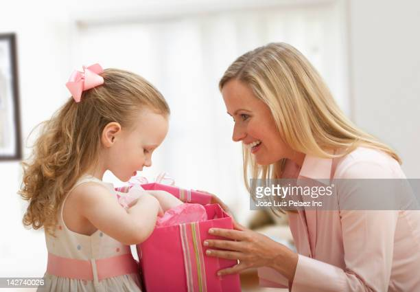 Caucasian mother giving daughter a gift
