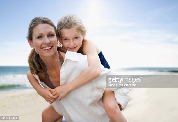 Caucasian mother giving daughter piggy back ride on beach