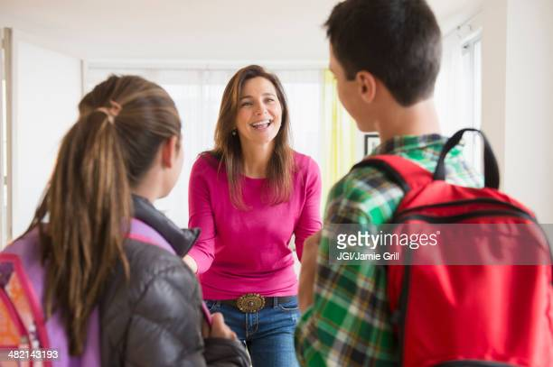 Caucasian mother greeting children with backpacks