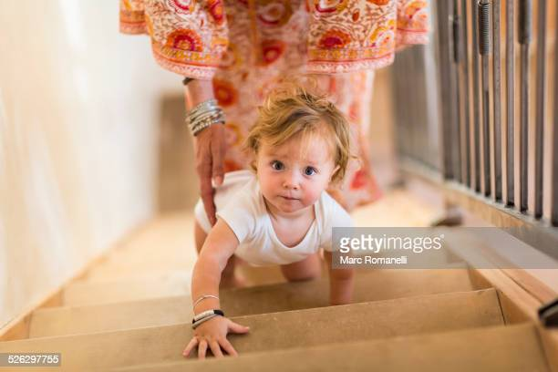 Caucasian mother helping baby son climb stairs