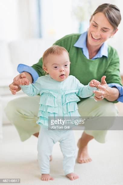 Caucasian mother helping baby with Down Syndrome walk