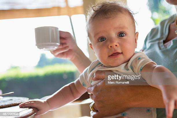 Caucasian mother holding baby at breakfast