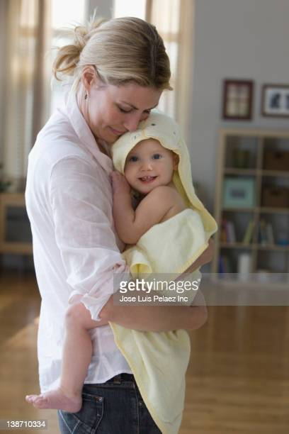 Caucasian mother holding baby daughter after bath