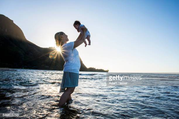 Caucasian mother holding baby in ocean on beach