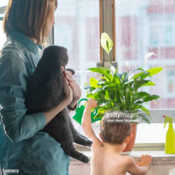 Caucasian mother holding cat watching son watering plant