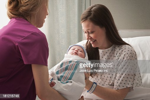 Caucasian mother holding newborn in hospital