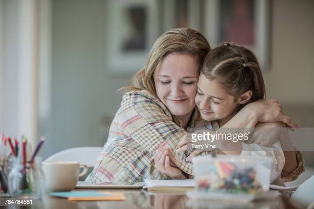 Caucasian mother hugging daughter at the table
