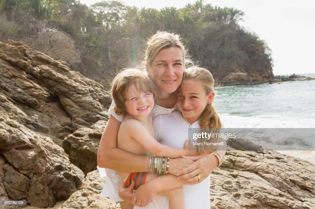 Caucasian mother hugging son and daughter at beach