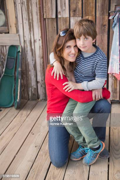 Caucasian mother hugging son on porch