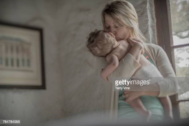 Caucasian mother kissing baby boy near window