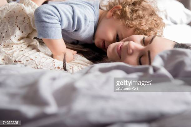 Caucasian mother laying on bed hugging son