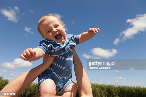 Caucasian mother lifting baby boy