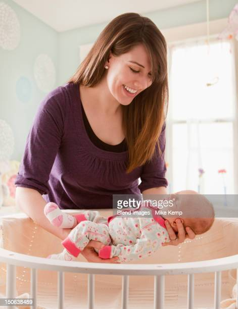 Caucasian mother lifting baby girl from crib