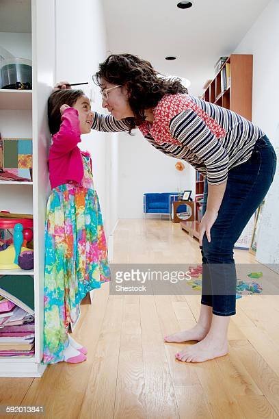 Caucasian mother measuring height of daughter on wall