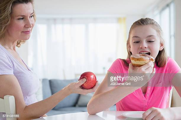 Caucasian mother offering daughter healthy food