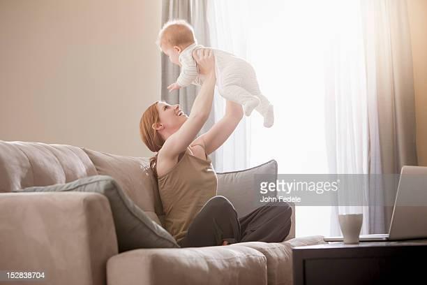 Personne de race blanche mère sur le canapé, levant son