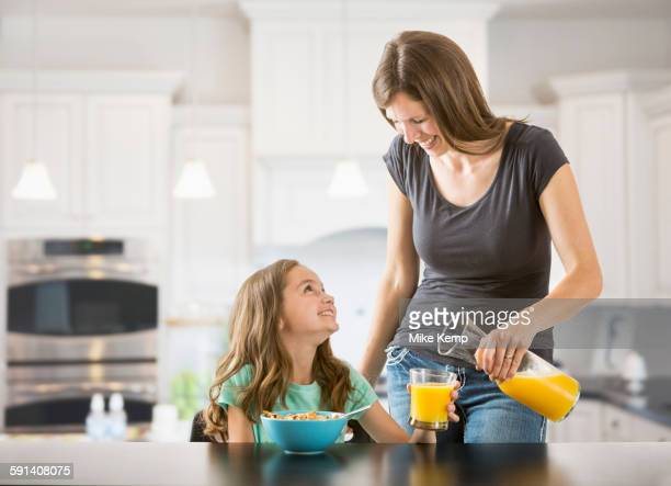 Caucasian mother pouring juice for daughter in kitchen