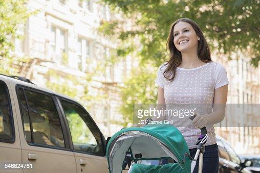 Caucasian mother pushing stroller on urban sidewalk
