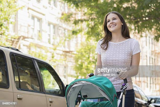 Caucasian mother pushing stroller on urban sidewalk