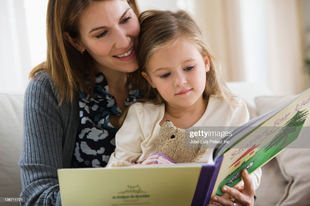 Caucasian mother reading book to daughter : Stock Photo