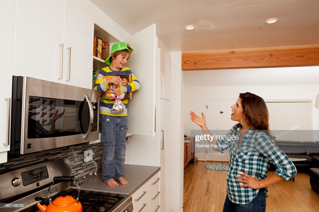 Caucasian mother scolding son on counter top : Stock Photo