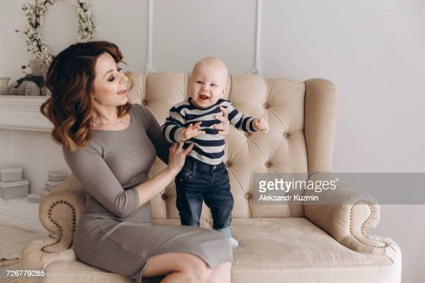 Caucasian mother sitting on love seat playing with baby son