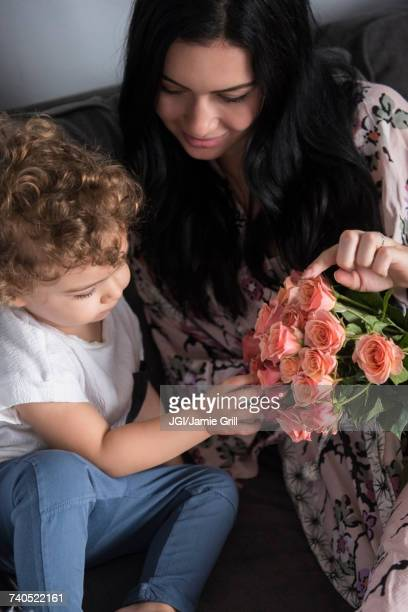 Caucasian mother sitting on sofa with son examining flowers
