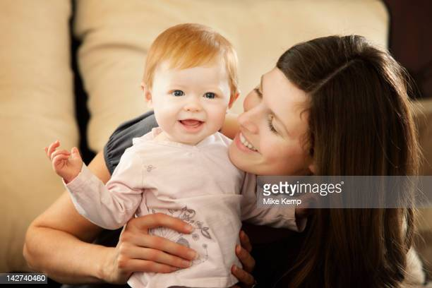 Caucasian mother smiling at baby daughter