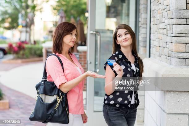 Caucasian mother taking daughter's credit card