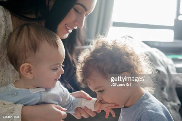 Caucasian mother watching son kiss hand of baby brother