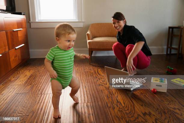 Caucasian mother watching toddler son walk