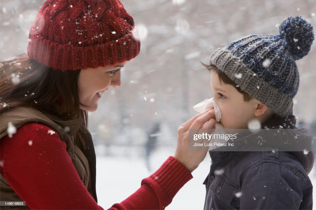 Caucasian mother wiping son's nose in the snow
