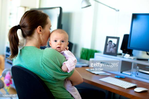 Caucasian mother working in home office and holding baby