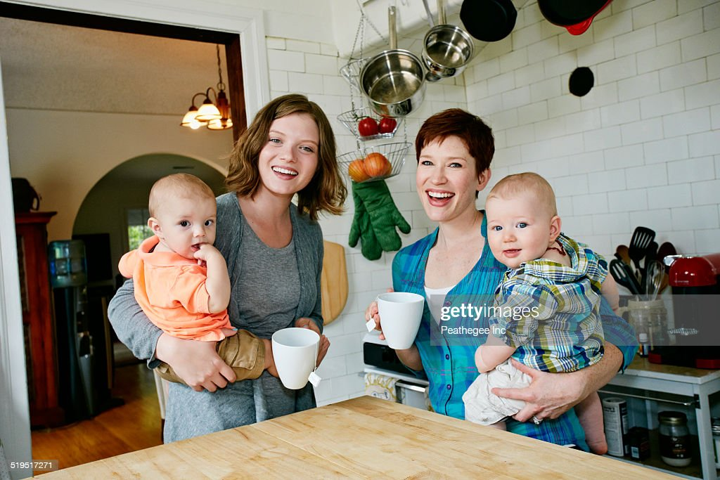 Caucasian mothers holding babies in kitchen