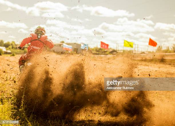 Caucasian motocross biker spraying dirt on race course
