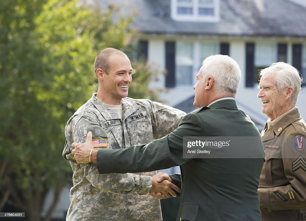 Caucasian multi-generation soldiers hugging outside