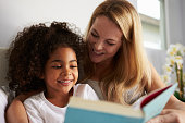 Caucasian mum and smiling black daughter read in bed, close-up